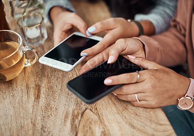 Buy stock photo Cropped shot of two women using their smartphones at a cafe