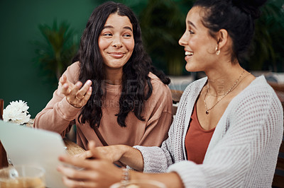 Buy stock photo Shot of young sisters using a digital tablet together at a cafe