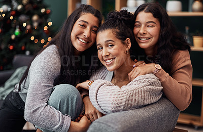 Buy stock photo Shot of young sisters relaxing on the sofa together during Christmas at home