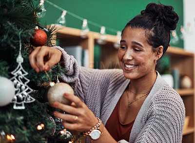 Buy stock photo Shot of a young woman decorating a Christmas tree at home