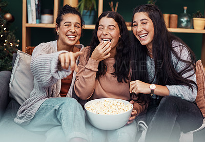 Buy stock photo Shot of young sisters having popcorn and watching tv together during Christmas at home