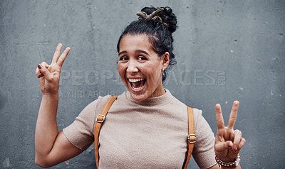 Buy stock photo Cropped portrait of an attractive teenage girl feeling playful and making a peace sign gesture against a gray city wall