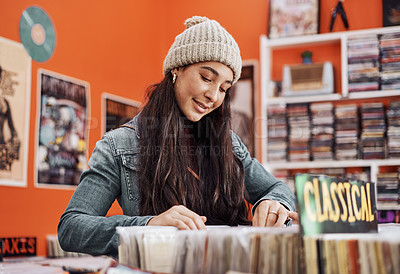 Buy stock photo Cropped shot of an attractive teenage girl standing alone and shopping for vinyl music records in the city