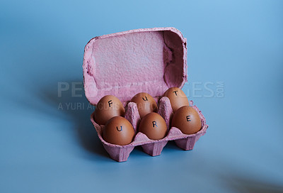 Buy stock photo Studio shot of a box against a blue background containing half a dozen eggs with the word future written on it
