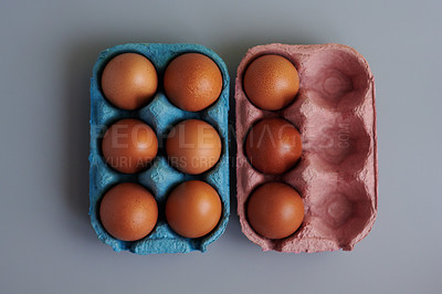 Buy stock photo Studio shot of chicken eggs in cartons against a grey background
