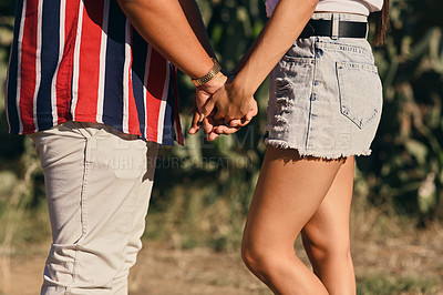 Buy stock photo Closeup shot of an unrecognisable couple holding hands outdoors