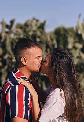 Buy stock photo Shot of an affectionate young couple kissing each other outdoors