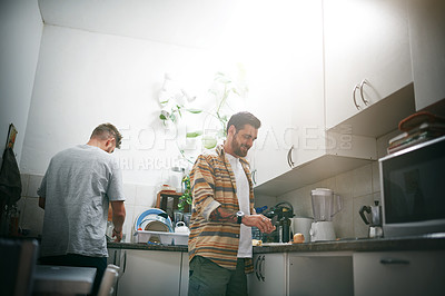Buy stock photo Cropped shot of two young men making food together in the kitchen at home during the day