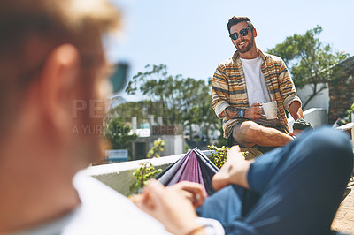 Buy stock photo Over the shoulder shot of a cheerful young man hanging out with his friend outside on their balcony at home