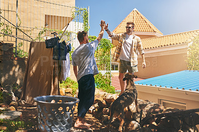 Buy stock photo High angle shot of two cheerful young men giving each other a high five for doing a great job in their washing outside at home