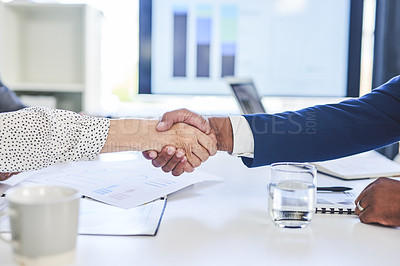 Buy stock photo Cropped shot of two unrecognizable businesspeople shaking hands during their boardroom meeting