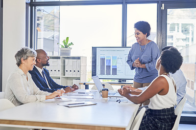 Buy stock photo Shot of an attractive young businesswoman pitching ideas to her colleagues inside a boardroom