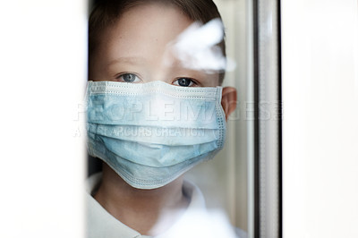 Buy stock photo Portrait of an adorable little boy wearing a surgical mask and looking out of a window at home