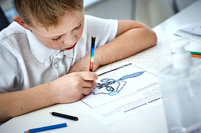 Buy stock photo Cropped shot of an adorable little boy drawing and doing his homework at home