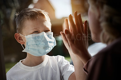 Buy stock photo Cropped shot of a little boy wearing a surgical mask giving his mother a high five through a glass window