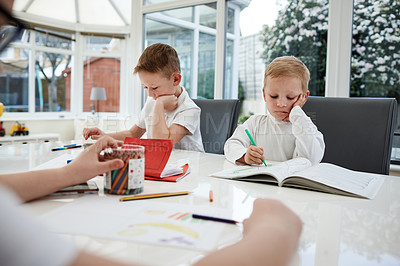 Buy stock photo Shot of three adorable young boys sitting together and doing their homework at home