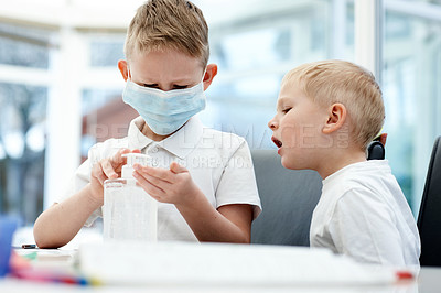 Buy stock photo Cropped shot of two adorable little boys sanitizing their hands before doing their schoolwork at home