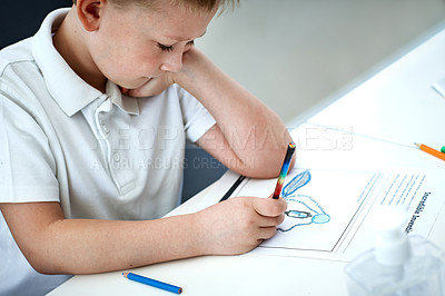Buy stock photo Cropped shot of an adorable little boy doing his homework at home