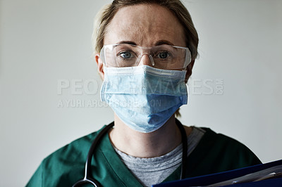 Buy stock photo Portrait of a female nurse wearing a surgical mask posing against a gray background
