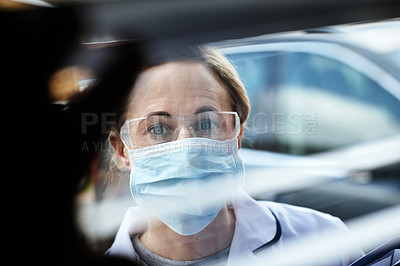 Buy stock photo Shot of a female healthcare worker wearing a surgical mask while looking through the window of a house