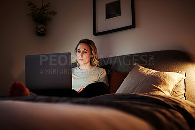 Buy stock photo Shot of an attractive young woman blogging on her laptop in her bedroom at home in the evening