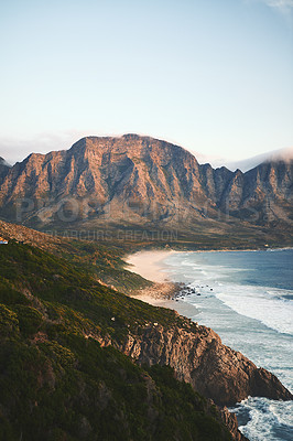 Buy stock photo Cropped shot of a mountain range near the sea during a clear day outdoors
