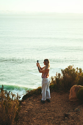 Buy stock photo Full length shot of an attractive young woman standing and taking pictures with her cellphone during a day outdoors