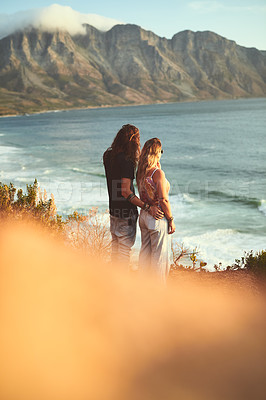 Buy stock photo Cropped shot of an affectionate young couple standing together and looking out at sea during a day outdoors