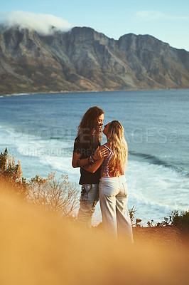 Buy stock photo Cropped shot of an affectionate young couple standing on the mountainside near a sea together during a day outdoors