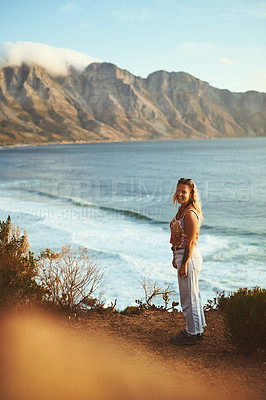 Buy stock photo Full length shot of an attractive young woman standing alone on a mountainside near the sea during a day outdoors