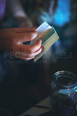 Buy stock photo Cropped shot of an unrecognizable man preparing to roll a joint of cannabis at home
