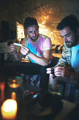 Buy stock photo Cropped shot of a handsome young man rolling a joint of cannabis while sitting with his friend at home