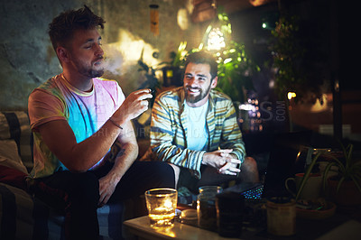 Buy stock photo Cropped shot of a handsome young man smoking cannabis while sitting with his friend at home