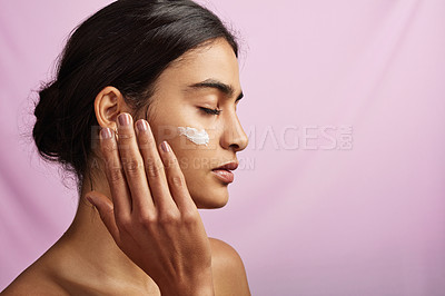 Buy stock photo Studio shot of a beautiful young woman applying moisturizer to her face