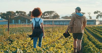 Buy stock photo Rearview shot of two young farmers working together in a crop field