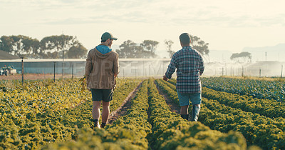 Buy stock photo Rearview shot of two handsome young male farmers working together in a crop field during the day