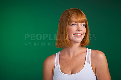 Buy stock photo Cropped shot of an attractive young sportswoman standing alone against a green background in the studio