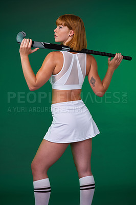 Buy stock photo Cropped shot of an attractive young sportswoman standing alone and posing with hockey stick against a green studio background