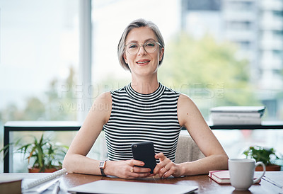 Buy stock photo Shot of a mature businesswoman using her cellphone while sitting at her desk