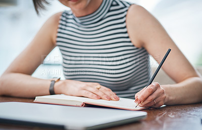 Buy stock photo Shot of an unrecognizable businesswoman writing in her notebook
