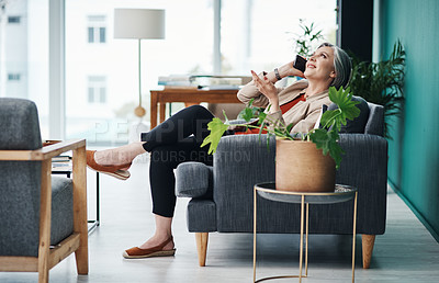 Buy stock photo Full length shot of an attractive mature businesswoman sitting alone and talking on her cellphone in her home office