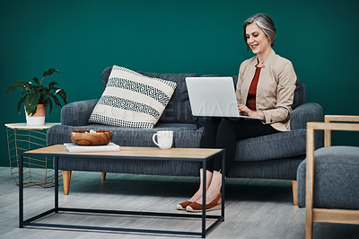 Buy stock photo Full length shot of an attractive mature businesswoman sitting alone and using a laptop in her home office