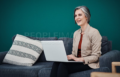 Buy stock photo Cropped shot of an attractive mature businesswoman sitting alone and using a laptop in her home office