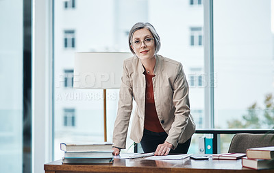 Buy stock photo Cropped portrait of an attractive mature businesswoman standing and reading paperwork by her desk in her home office
