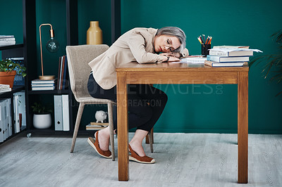 Buy stock photo Full length shot of an attractive mature businesswoman asleep at her desk in her home office