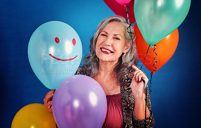 Buy stock photo Portrait of a cheerful senior woman posing holding balloons in studio against a blue background