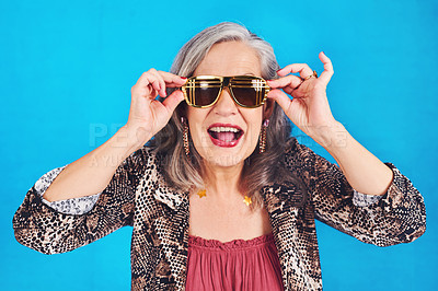 Buy stock photo Portrait of a funky and stylish senior woman wearing sunglasses posing against a blue background
