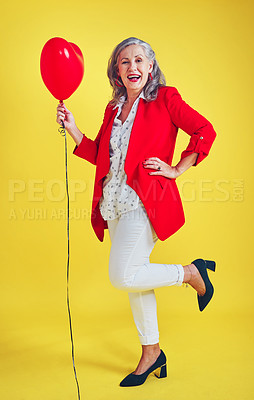 Buy stock photo Full length shot of a funky and stylish senior woman posing while holding a balloon in studio