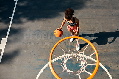 Buy stock photo High angle shot of a sporty young woman playing basketball on a sports court