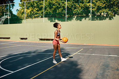 Buy stock photo Shot of a sporty young woman playing basketball on a sports court